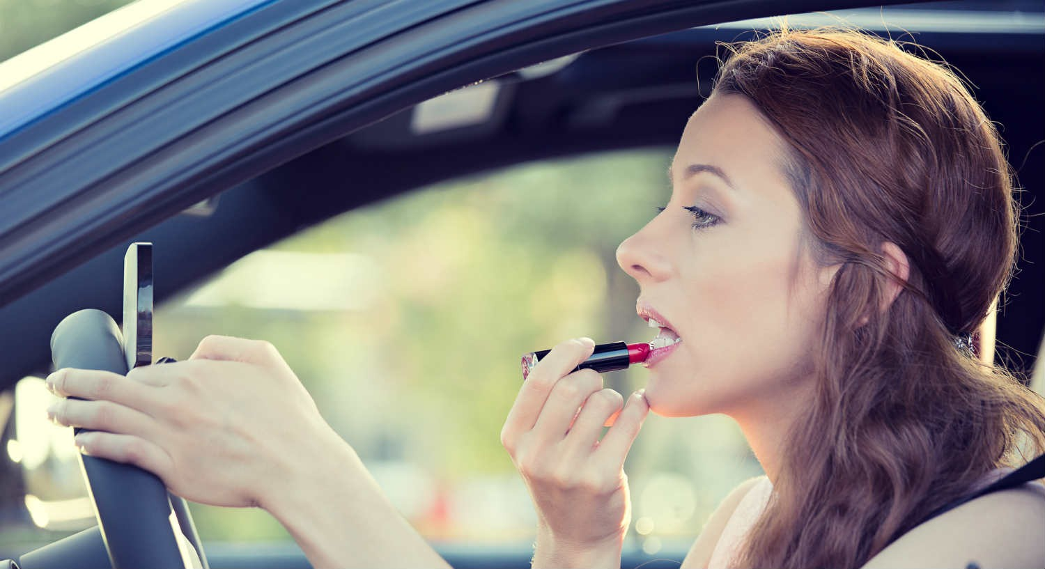 woman putting lipstick on in car